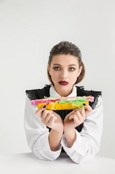 We zijn wat we eten. vrouw eet hotdog gemaakt van plastic, eco-concept. er zijn zoveel polymeren dat we er gewoon van gemaakt zijn. milieuramp, mode, schoonheid, eten. organische wereld verliezen.