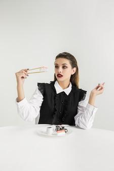 We zijn wat we eten. vrouw eet sushi gemaakt van plastic, eco-concept. er zijn zoveel polymeren dat we er gewoon van gemaakt zijn. milieuramp, mode, schoonheid, eten. verloren organische wereld.