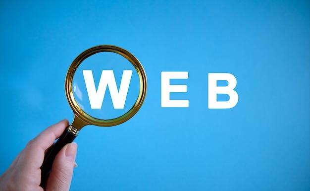 Web - tekst met een vergrootglas op een blauwe achtergrond