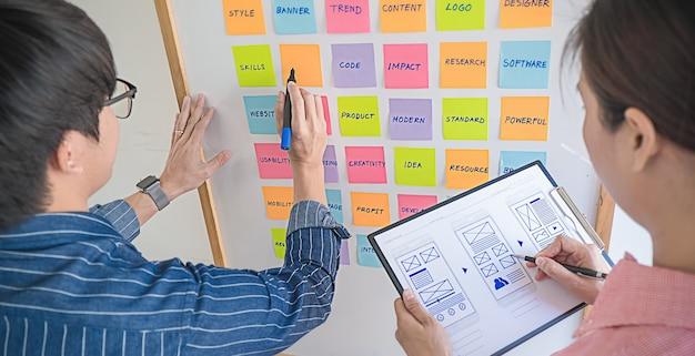 Webdesigner brainstormen voor een strategieplan. kleurrijke plaknotities met dingen om te doen op kantoorbord. gebruikerservaring (ux) concept.