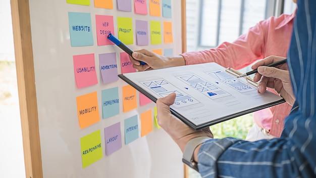 Webdesigner brainstormen voor een strategisch plan. kleurrijke plaknotities met dingen om te doen op kantoor boord. gebruikerservaring (ux) concept.