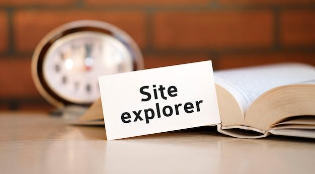 Websiteverkenner tekst op een wit oppervlak met een klok en een open boek