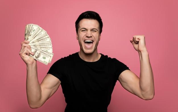 Wedden op sport. jonge dolgelukkige man in vrijetijdskleding, die een hoop dollars in zijn rechterhand houdt en schreeuwt van vreugde.
