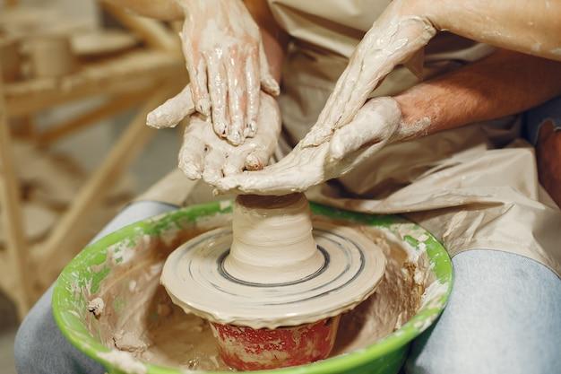 Wederzijds creatief werk. handen die een kom op een aardewerkschijf creëren in een kleistudio.