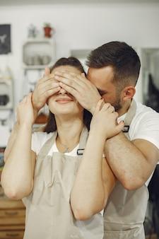 Wederzijds creatief werk. jong mooi paar in vrijetijdskleding en schorten. mensen houden keramische schalen vast.