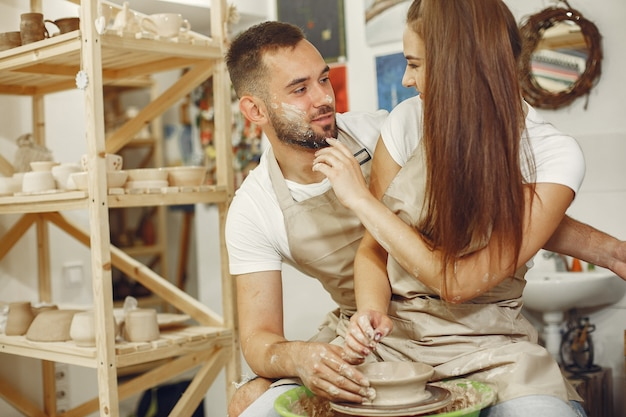 Wederzijds creatief werk. jong mooi paar in vrijetijdskleding en schorten. mensen maken een kom op een aardewerkschijf in een kleistudio.
