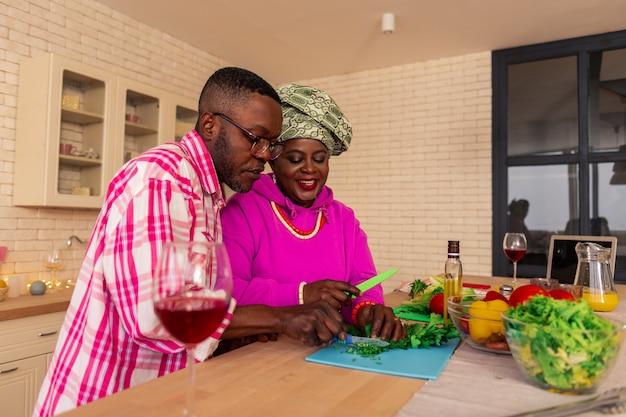 Wederzijdse ondersteuning. aangename aardige man die naast zijn vrouw staat terwijl hij haar helpt in de keuken