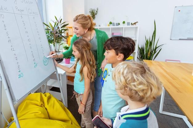 Wedstrijd zwerfvuil sorteren. drie hardwerkende leerlingen doen mee aan afvalsorteerwedstrijd bij de les ecologie