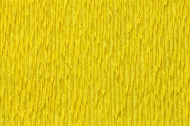 Weefsel gele achtergrond van golvend golfdocument, close-up.