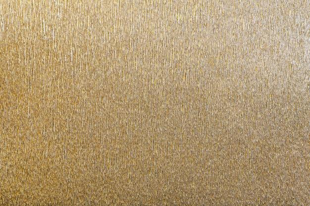 Weefsel van gouden achtergrond van golvend golfdocument, close-up.