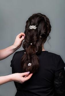 Weefsel, vlechtstaartkapsel. kapper die kapsel maakt aan bruine haarvrouw met lang haar op grijze achtergrond