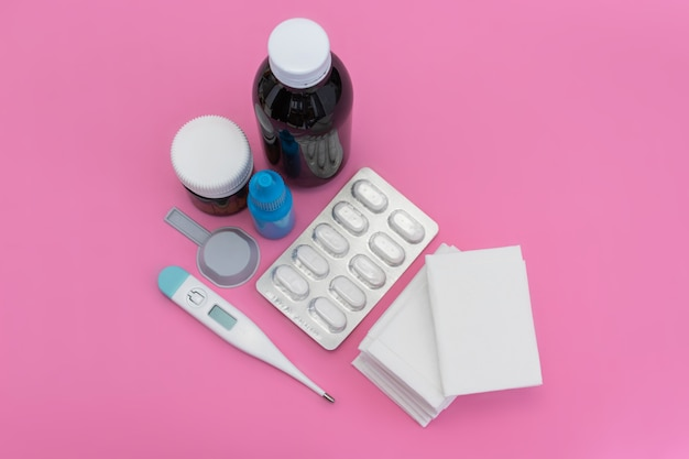 Weefsels, neusdruppels, thermometer, pillen en blister op roze achtergrond. bovenaanzicht. plat leggen