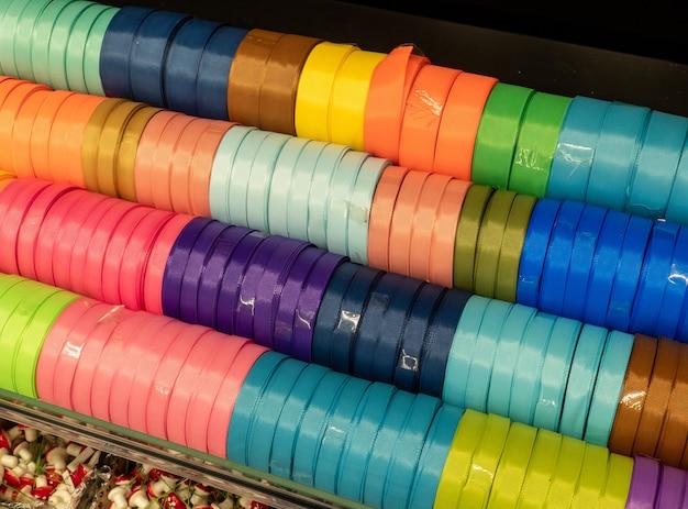 Weefselzijden linten op een plank in een winkel. zelfgemaakt concept. veelkleurige linten in de winkel voor handwerk.