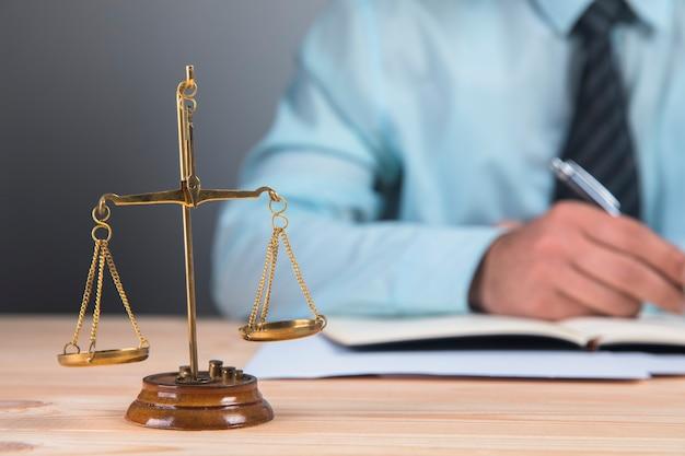 Weegschaal en de rechter schrijft op papier op een grijze ondergrond