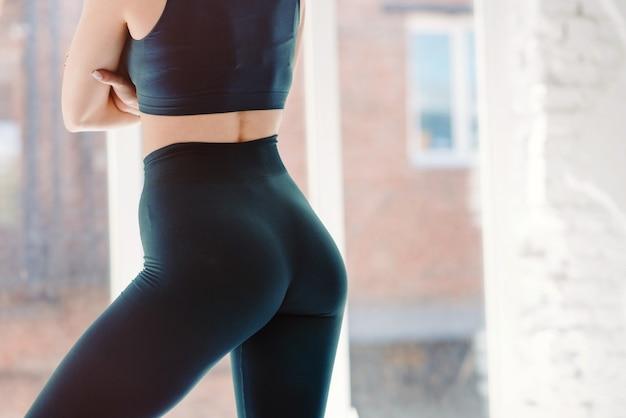 Weegtloss wellness eten voeding vitaliteit concept. bijgesneden close-up foto van seksueel sportief sportief verleidelijk mooie aantrekkelijke mooie ronde kont dragen blauwe strakke broek leggings