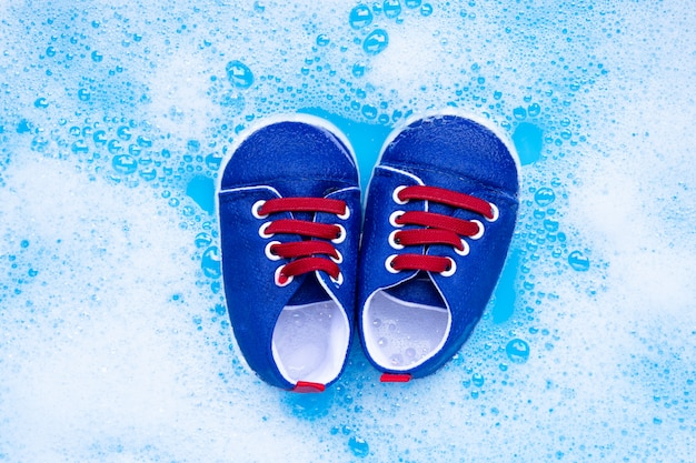 Week babyschoenen in het babywasmiddel om water op te lossen voor het wassen. wasserij concept,