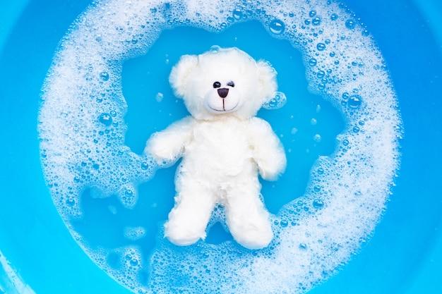 Week de speelgoedbeer voor het wassen in wasmiddeloplossing in water. wasserette,