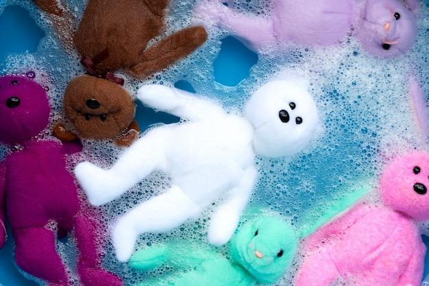 Week de speelgoedteddybeer voor het wassen in het water van het wasmiddel.