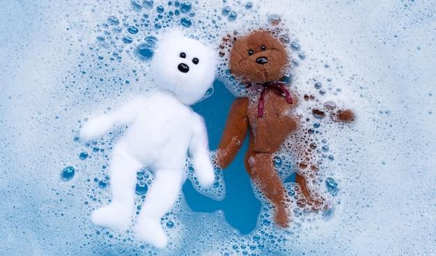 Week de speelgoedteddybeer voor het wassen in het water van wasmiddel.