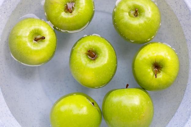 Week groene appels in water. fruit concept wassen