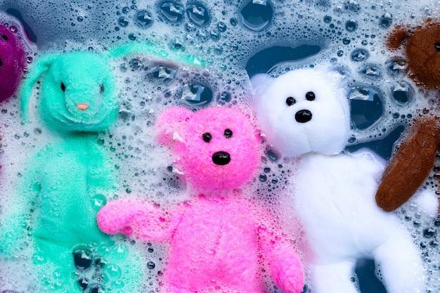 Week konijn pop met speelgoed teddybeer in wasmiddel water oplossen voor het wassen. wasserij concept