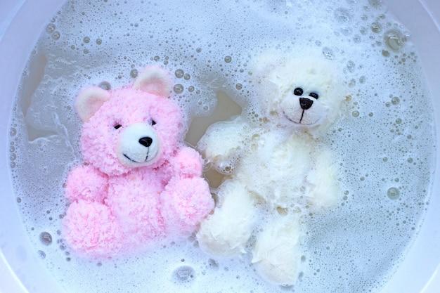 Week speelgoedberen in het oplossen van wasmiddel in water voordat ze worden gewassen. wasserij concept, bovenaanzicht
