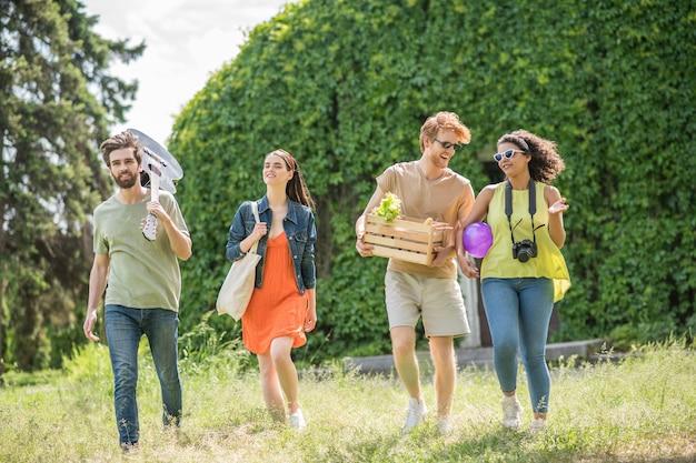 Weekend, rust. twee jonge lange jongens met gitaar en doos met eten en vriendinnen gaan picknicken op een zonnige dag in een vrolijke bui