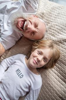 Weekenden. een man die met zijn kleinzoon in een bed blijft