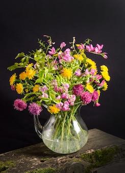 Weelderig boeket van wilde bloemen in een vaas op een zwarte ruimte in een donkere stijl, bloemstilleven