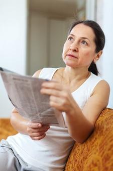 Weemoedige vrouw met krant