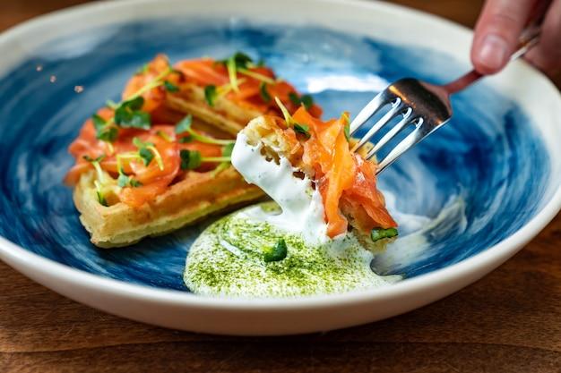 Weense wafel met zalm en witte saus op een blauw bord wordt gegeten met een mes en vork. ontbijt serveren in een café en restaurant. het serveren van de tafel en het serveren van gerechten voor het banket.