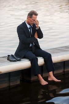 Weer mislukt. depressieve volwassen zakenman die zijn gezicht met de hand aanraakt terwijl hij op blote voeten aan de kade zit