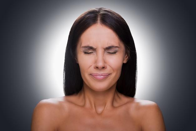 Weer mislukt! portret van gefrustreerde jonge shirtloze vrouw die de ogen gesloten houdt