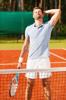 Weer verliezen. gefrustreerde jonge man in sportkleding die zijn hoofd met de hand aanraakt en de ogen gesloten houdt terwijl hij een tennisracket vasthoudt en op de tennisbaan staat