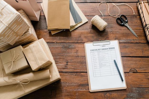 Weergave van checklistpapier, pen, verpakte dozen, draden, schaar en stapel blocnotes op hout