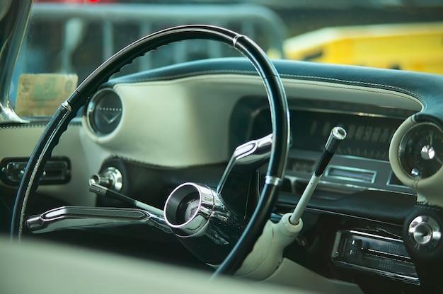 Weergave van dashboard, stuurwiel, indicatoren en timing meters van een vintage amerikaanse auto met alle details van het interieur zichtbaar.