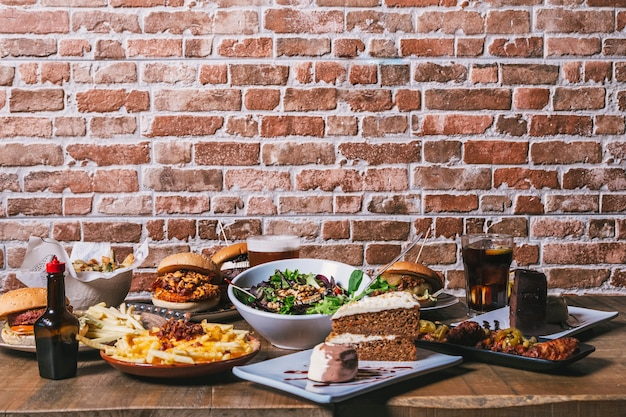 Weergave van de tafel met een verscheidenheid aan gerechten, hamburgers, friet en salade, drankjes, kippenvleugels, saus, cake en desserts op de houten tafel. restaurant menu.