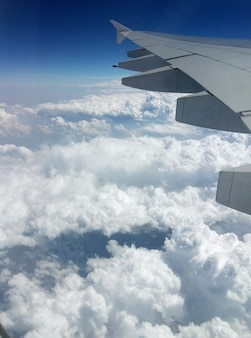 Weergave van de vleugel van een passagiersvliegtuig uit de patrijspoort in de lucht