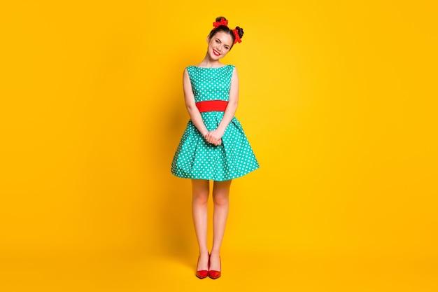 Weergave van de volledige lengte van het lichaam van een charmant vrolijk meisje dat een groenblauwe jurk draagt, een goede feestlook die geïsoleerd is op een felgele kleurachtergrond