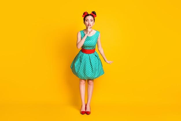 Weergave van de volledige lengte van het lichaam van een leuk mooi meisje dat een groenblauwe gestippelde jurk draagt met een shh-teken dat over een felgele kleurachtergrond wordt geïsoleerd
