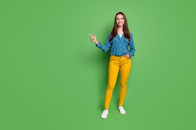 Weergave van de volledige lengte van het lichaam van een leuk uitziend, vrolijk slank meisje dat een kopie van de ruimteadvertentie toont die op een felgroene kleurachtergrond is geïsoleerd
