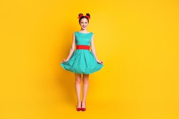 Weergave van de volledige lengte van het lichaam van een mooi vrolijk meisje met een groenblauwe jurk die zich voordeed op een felgele achtergrond