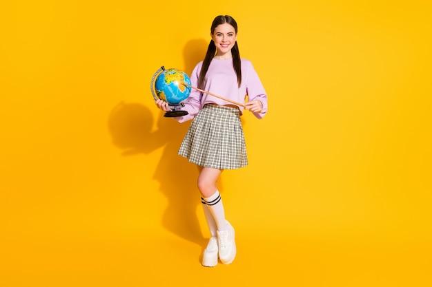 Weergave van de volledige lengte van het lichaam van een slim meisje dat een wereldbol in de hand houdt die naar het land wijst