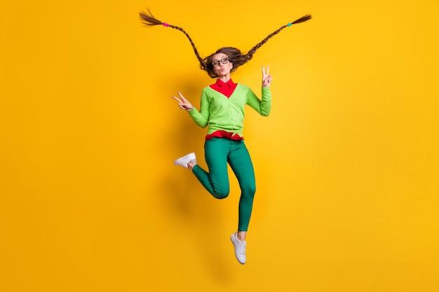 Weergave van de volledige lengte van het lichaam van een vrij funky komisch vrolijk meisje dat springt en een luchtkus verzendt met een v-teken geïsoleerd felgele kleur achtergrond