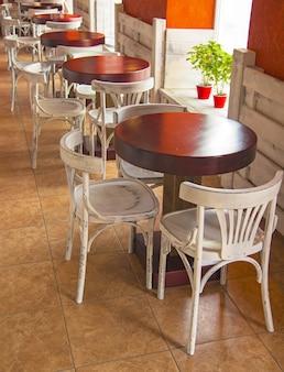 Weergave van een café met lege tafels en stoelen.