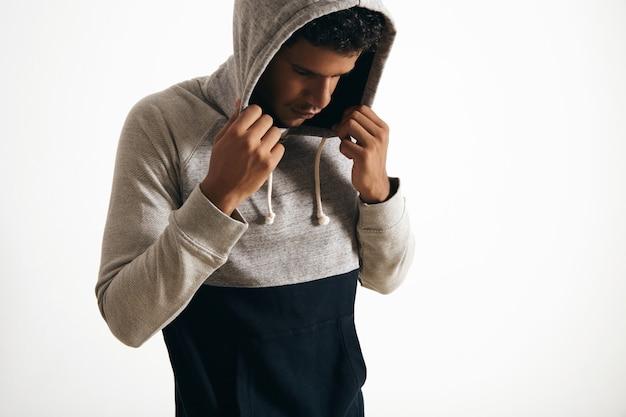 Weergave van een donkere man die naar beneden kijkt, draagt zijn kap met zijn handen, zijaanzicht