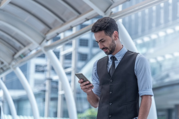 Weergave van een jonge aantrekkelijke bedrijfsmens die smartphone gebruikt