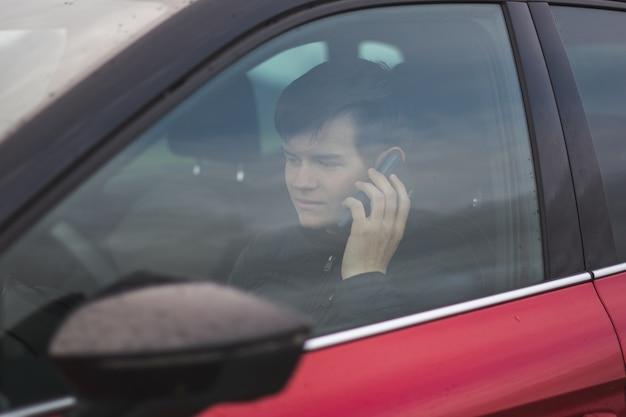 Weergave van een jonge man die een zwarte jas draagt die in een rode auto zit terwijl hij aan de telefoon zit