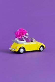 Weergave van een kleine kleurrijke gele auto waarin er een geschenkdoos met een strik op een paars. concept vakantie, vervoer, valentijnsdag, speelgoed