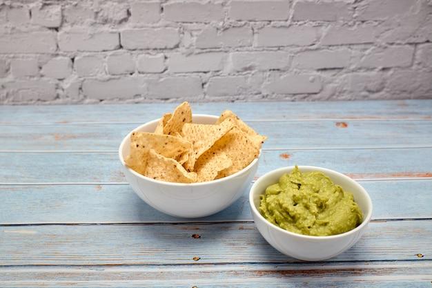 Weergave van een kom met pittige guacamole naast een kom met nacho's